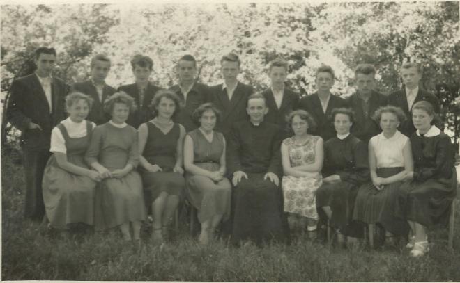 """Po latach przerwy """"odwilży"""" po październiku 1956 r. mogła wrócić nauka religii. Na zdjęciu z 19.06.1957 klasa IIIa z księdzem B. Siedleckim. Od lewej siedzą Władzia Orłowska, Sabina Ciesielczuk, Genia Roman,  Ania Skiba, Celina Bieńkowska, Teresa Błaszczak, Teresa Jezierska, Teresa Górska. Stoją od lewej Stefan Drężek, Piotr Prud, Heniek Florek, Tadek Ruszczyński, Edek Jaroń, Wiesiek Chludziński, Wacek Łojko, Waldek Rakowski, Marian Jechna."""